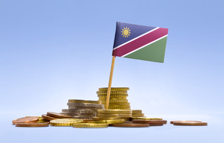 economizing: Flag of Namibia in a mixed stack of european coins and a blue background.(series)