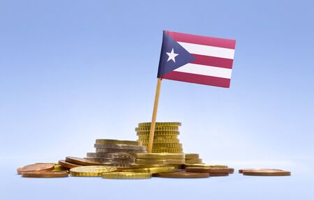 puerto rican flag: Flag of Puerto Rico in a mixed stack of european coins and a blue background.(series) Stock Photo
