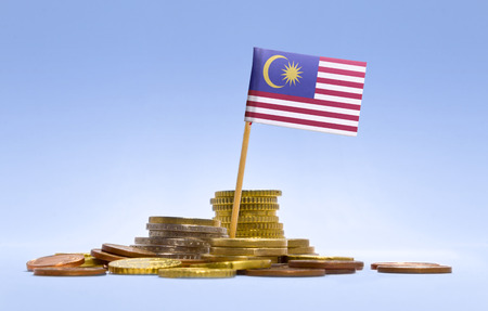 malaysia: Flag of Malaysia in a mixed stack of european coins and a blue background.(series)