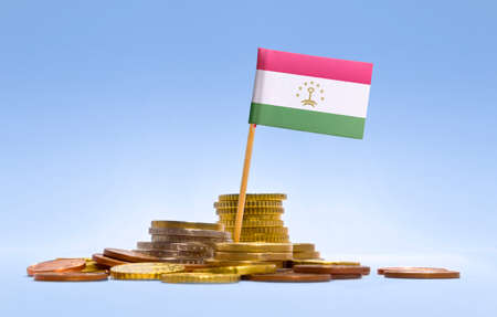 economy of tajikistan: Flag of Tajikistan in a mixed stack of european coins and a blue background.(series) Stock Photo
