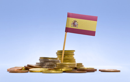Flag of Spain in a mixed stack of european coins and a blue background.(series) Stock Photo