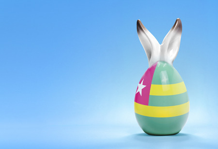 Colorful cute ceramic easter egg with rabbit ears and the flag of Togo .(series) photo