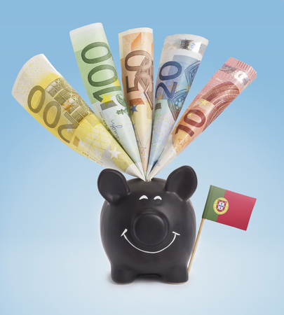 twenty euro banknote: Ten,twenty,fifty,one hundred and a 200 Euro banknote in a smiling piggybank of Portugal.(series)