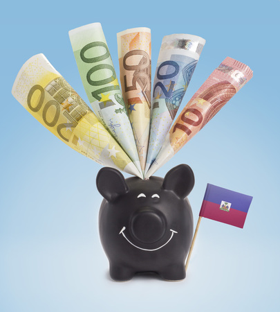 fifty euro banknote: Ten,twenty,fifty,one hundred and a 200 Euro banknote in a smiling piggybank of Haiti.(series) Stock Photo