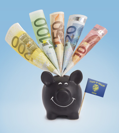 fifty euro banknote: Ten,twenty,fifty,one hundred and a 200 Euro banknote in a smiling piggybank of Oregon.(series)