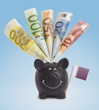 twenty euro banknote: Ten,twenty,fifty,one hundred and a 200 Euro banknote in a smiling piggybank of Qatar.(series) Stock Photo