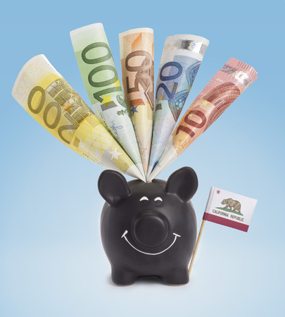 Ten,twenty,fifty,one hundred and a 200 Euro banknote in a smiling piggybank of California.(series) photo