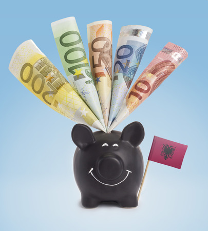 fifty euro banknote: Ten,twenty,fifty,one hundred and a 200 Euro banknote in a smiling piggybank of Albania.(series)