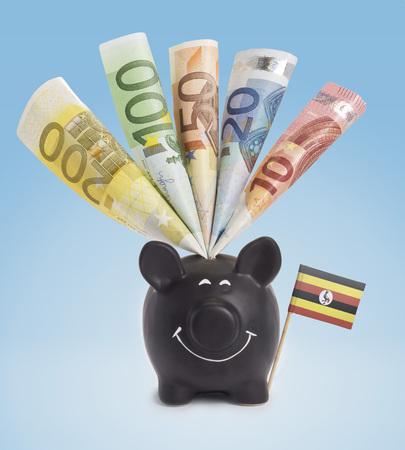 twenty euro banknote: Ten,twenty,fifty,one hundred and a 200 Euro banknote in a smiling piggybank of Uganda.(series) Stock Photo