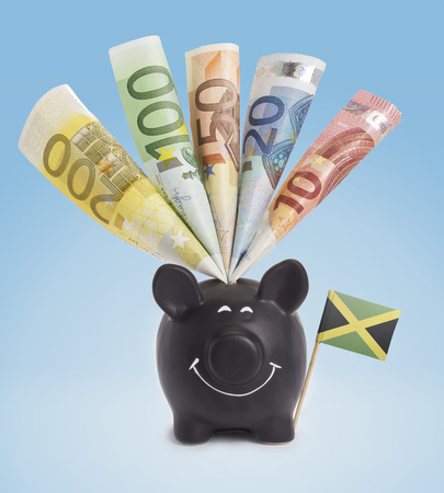 fifty euro banknote: Ten,twenty,fifty,one hundred and a 200 Euro banknote in a smiling piggybank of Jamaica.(series)