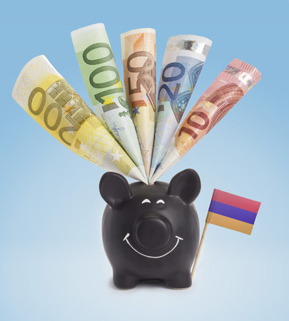 fifty euro banknote: Ten,twenty,fifty,one hundred and a 200 Euro banknote in a smiling piggybank of Armenia.(series)