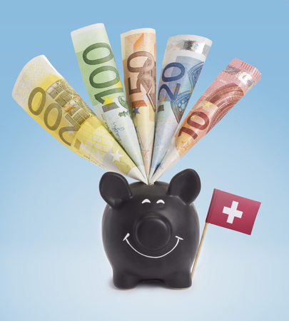 twenty euro banknote: Ten,twenty,fifty,one hundred and a 200 Euro banknote in a smiling piggybank of Switzerland.(series)