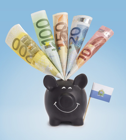 twenty euro banknote: Ten,twenty,fifty,one hundred and a 200 Euro banknote in a smiling piggybank of San Marino.(series)