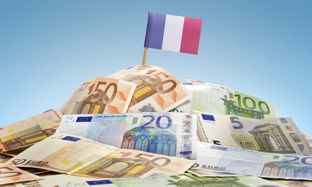 The national flag of France sticking in a pile of mixed european banknotes.(series) Stock Photo