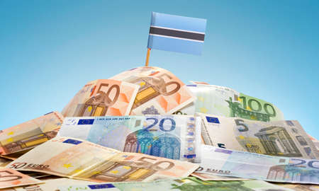 botswanan: The national flag of Botswana sticking in a pile of mixed european banknotes.(series) Stock Photo