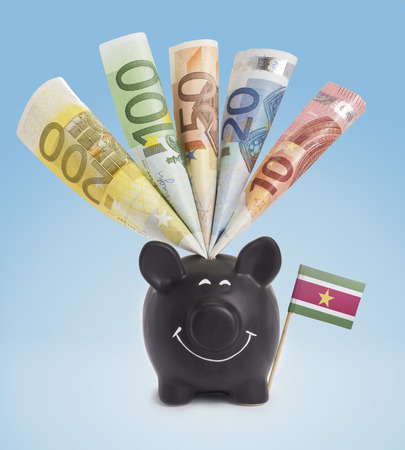 fifty euro banknote: Ten,twenty,fifty,one hundred and a 200 Euro banknote in a smiling piggybank of Suriname.(series) Stock Photo
