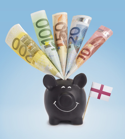 Ten,twenty,fifty,one hundred and a 200 Euro banknote in a smiling piggybank of England.(series) photo