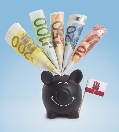 fifty euro banknote: Ten,twenty,fifty,one hundred and a 200 Euro banknote in a smiling piggybank of Gibraltar.(series)