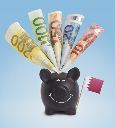 fifty euro banknote: Ten,twenty,fifty,one hundred and a 200 Euro banknote in a smiling piggybank of Bahrain.(series)