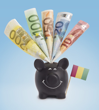 twenty euro banknote: Ten,twenty,fifty,one hundred and a 200 Euro banknote in a smiling piggybank of Guinea.(series)