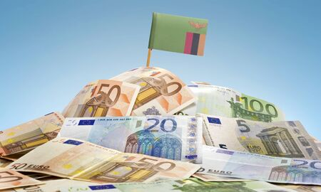 zambian: The national flag of Zambia sticking in a pile of mixed european banknotes.(series)