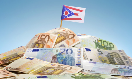 The national flag of Ohio sticking in a pile of mixed european banknotes.(series) photo