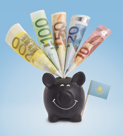 twenty euro banknote: Ten,twenty,fifty,one hundred and a 200 Euro banknote in a smiling piggybank of Kazakhstan.(series)