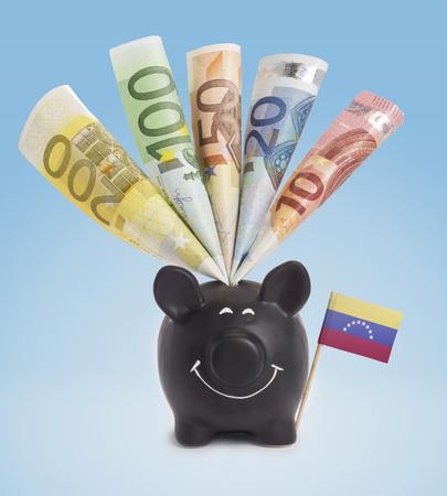 twenty euro banknote: Ten,twenty,fifty,one hundred and a 200 Euro banknote in a smiling piggybank of Venezuela.(series) Stock Photo