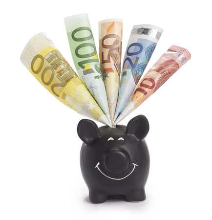 black money: A very happy black piggybank stuffed with various euro banknotes. (Also suitable for black money)