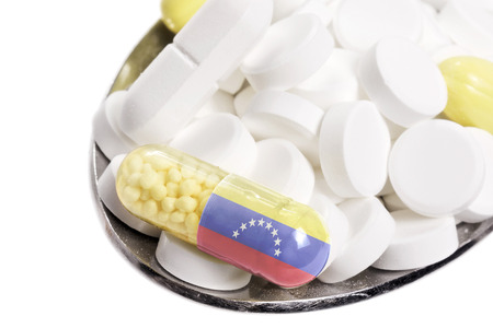 The national flag of Venezuela on a capsule and pills on a spoon.(series) Stock Photo