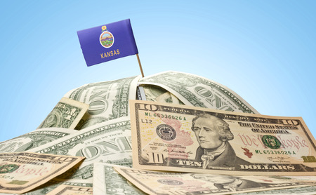 financial market: The national flag of Kansas sticking in a pile of american dollars.(series)