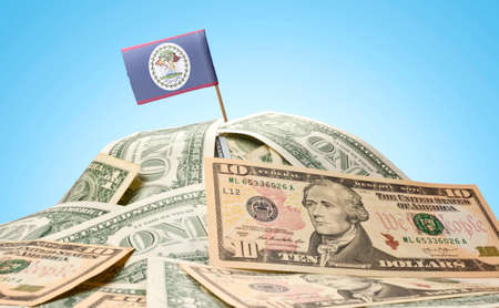 american currency: The national flag of Belize sticking in a pile of american dollars
