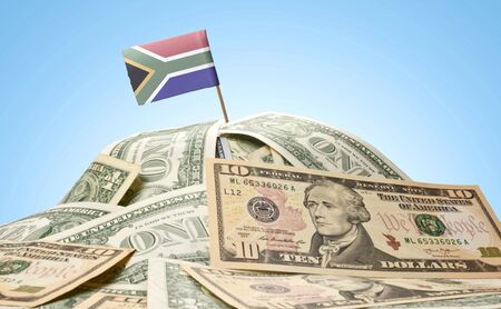 The national flag of South Africa sticking in a pile of american dollars