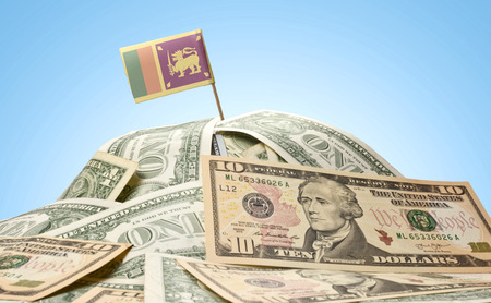 sri lankan flag: The national flag of Sri Lanka sticking in a pile of american dollars