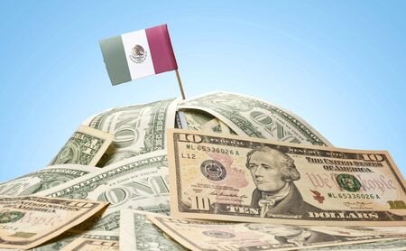 The national flag of Mexico sticking in a pile of american dollars