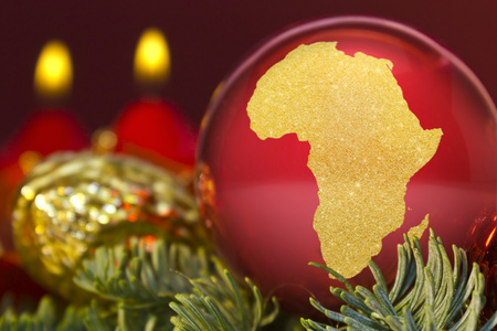 A glossy red bauble with the golden shape of Africa.(series)