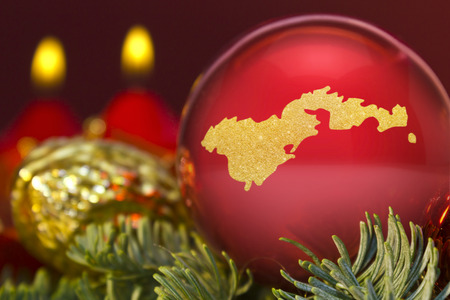 A glossy red bauble with the golden shape of American Samoa.(series)