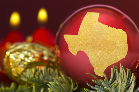 A glossy red bauble with the golden shape of Texas.(series)