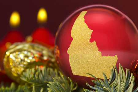 A glossy red bauble with the golden shape of Idaho.(series) Stock Photo