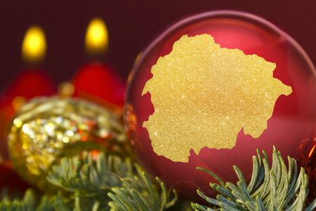 A glossy red bauble with the golden shape of Andorra.(series)