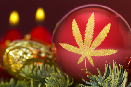 A glossy red bauble with the golden shape of a weed leaf.(series) Stock Photo