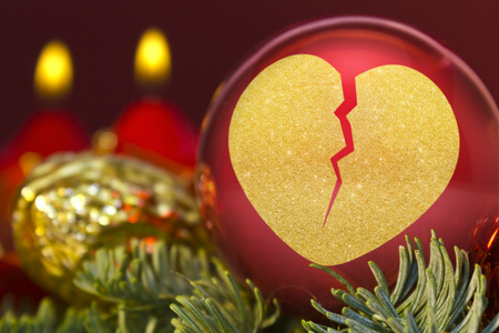 A glossy red bauble with the golden shape of a broken heart.(series) Stock Photo