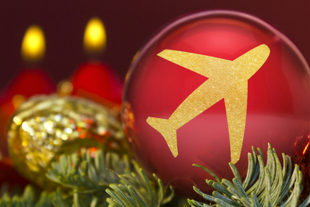 A glossy red bauble with the golden shape of an aeroplane.(series) Stock Photo