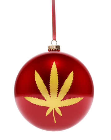 gold leaf: A hanging glossy red bauble with the golden shape of a weed leaf.(series) Stock Photo