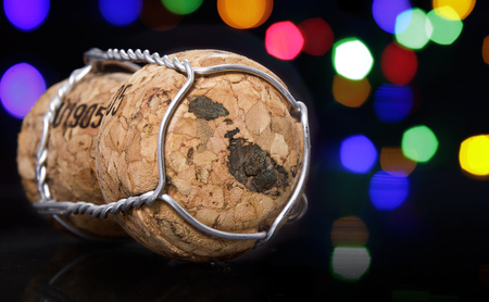 Champagne cork with the shape of Malta burnt in and colorful blurry lights in the background.(series)