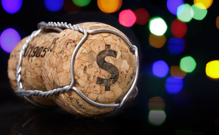 Champagne cork with the shape of a Dollar symbol burnt in and colorful blurry lights in the background.(series) Stock Photo