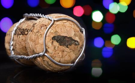 Champagne cork with the shape of Jamaica burnt in and colorful blurry lights in the background.(series) Stock Photo