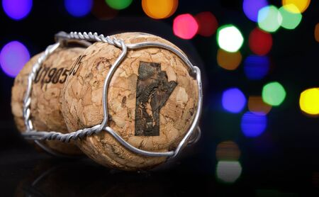 manitoba: Champagne cork with the shape of Manitoba burnt in and colorful blurry lights in the background.(series)