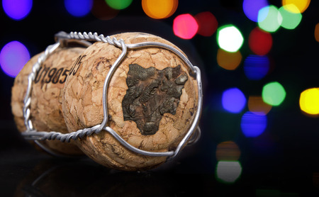 Champagne cork with the shape of Nigeria burnt in and colorful blurry lights in the background.(series)