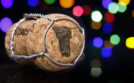 Champagne cork with the shape of Namibia burnt in and colorful blurry lights in the background.(series)